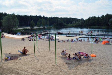 Plaża na Krubinie. Na pierwszym planie znajdują się dwa żagle przeciwsłoneczne. To duże, białe, trójkątne kawałki tkaniny, rozwieszonej na trzech wysokich i cienkich słupach. Tkanina daje cień, w którym można się schować przed palącym słońcem. Pod żaglami siedzi kilka osób. W głębi znajduje się dalsza część plaży i kąpielisko z pomostem. W głębi zdjęcia widać drzewa, rosnące wokół zbiornika wodnego.