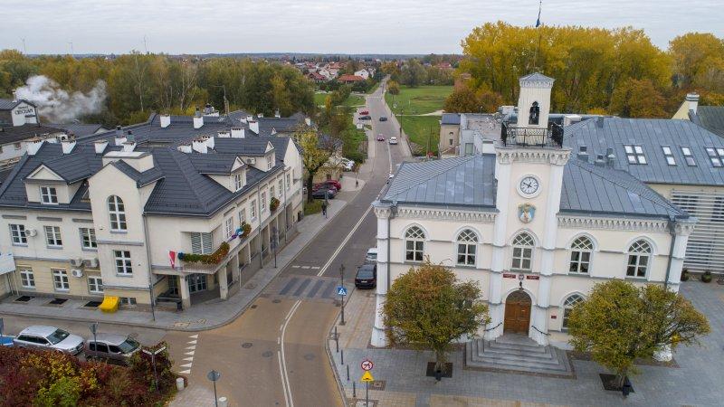Zdjęcie wykonane z lotu ptaka. Po prawej stoi ratusz, po lewej budynek przy ul. Wodnej. Ulica Wodna dzieli oba budynki.