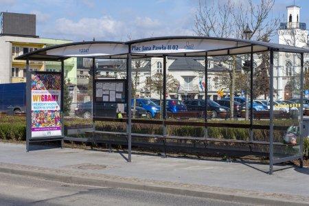 Przystanek autobusowy przy placu Jana Pawła II. Przez oszklone ściany można zobaczyć siedzibę Urzędu Miasta: fragment ratusza i budynku przy ulicy Wodnej.
