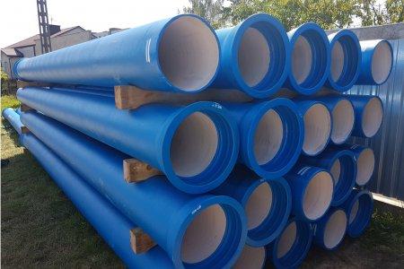 Na trawie niebieskie leżą rury o dużej średnicy ułożone pięć w poziomie na cztery w pionie.