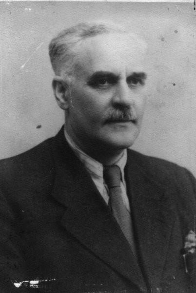 Fotografia doktora Szwanke. Mężczyzna w średnim wieku, ma siwe, zaczesane do tyłu włosy, gęste czarne brwi i siwe wąsy. Twarz pociągła. Ubrany jest w marynarkę, białą koszulę i krawat.